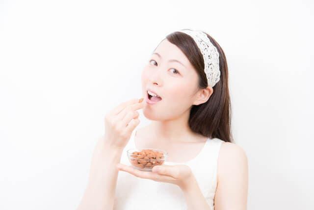 ナッツを食べる女