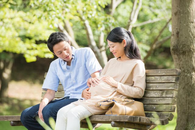 妊娠中のお腹を触る夫婦