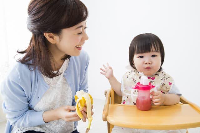 バナナを持つ母親と幼児