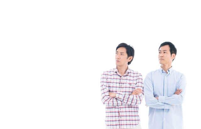 腕を組む2人の男性