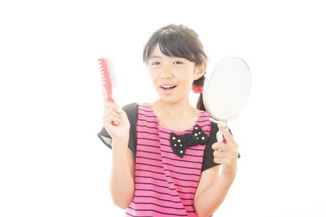 鏡とブラシを持つ女の子