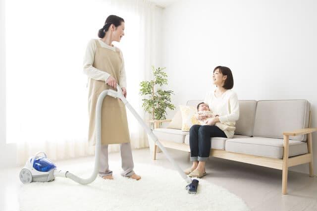 掃除機をかける女性と赤ちゃんを抱く女性