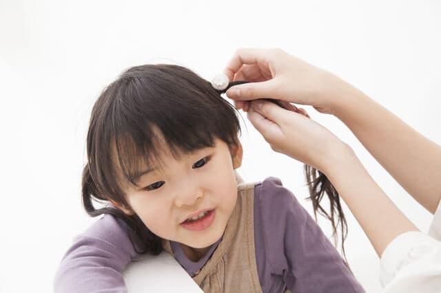 髪を結んでもらう女の子