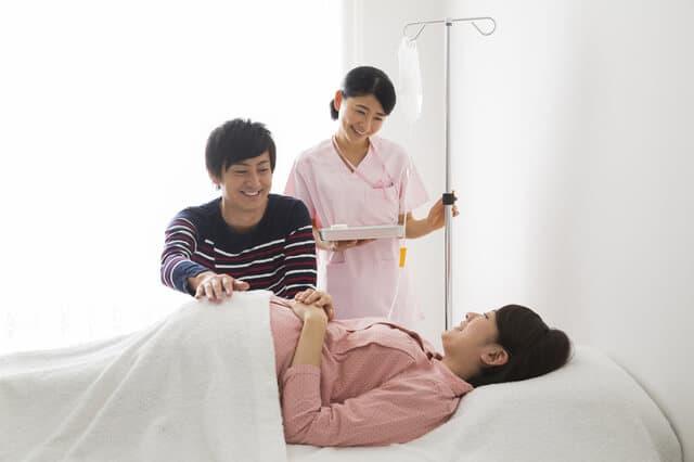 ベッドの上の笑顔の妊婦さん