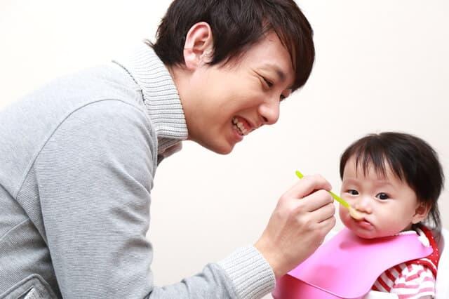 赤ちゃんにごはんをあげるパパ