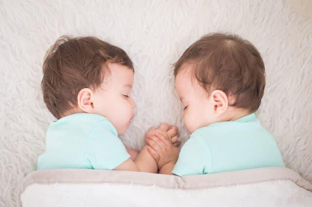 手を繋いで眠る双子の男の子
