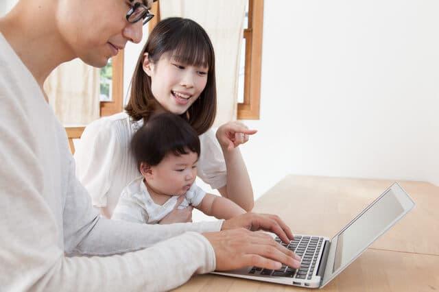 パソコンを見る若い家族