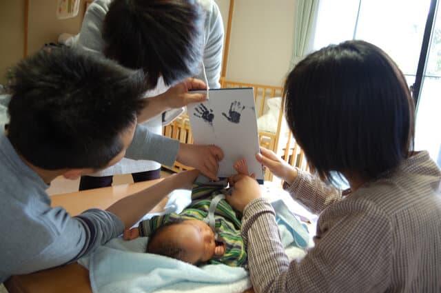 赤ちゃんの手形をとる家族