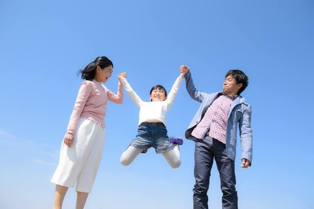 手をつなぐ夫婦と子供