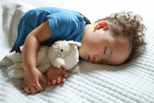 人形を抱きながら寝ている子ども