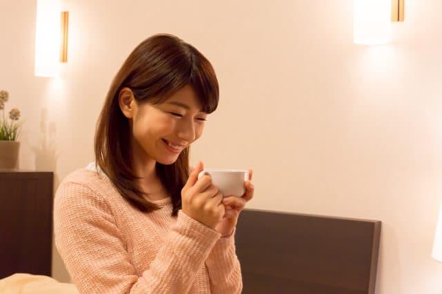 部屋でコーヒーを飲む女性