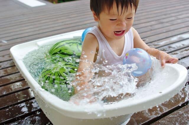 スイカと一緒に桶に入る赤ちゃん