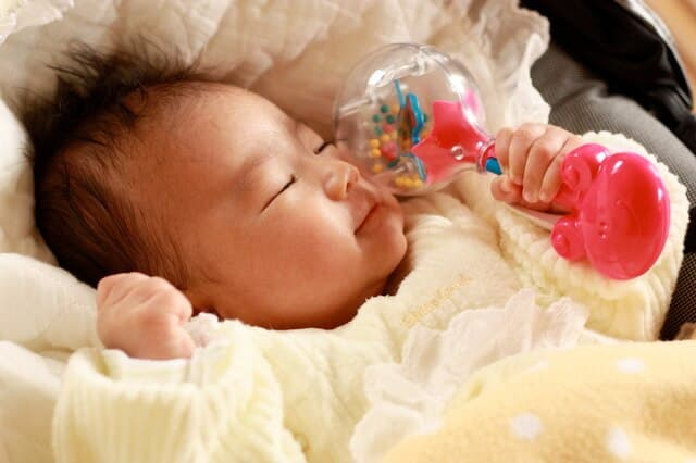 おもちゃを持ちながら寝る赤ちゃん