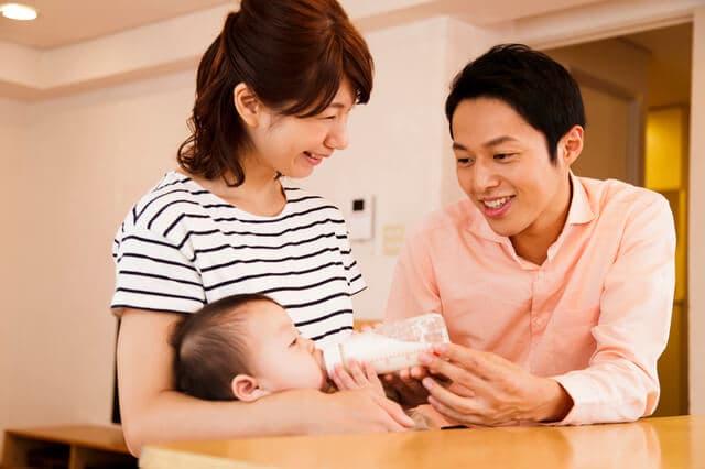赤ちゃんにミルクを飲ませる夫婦