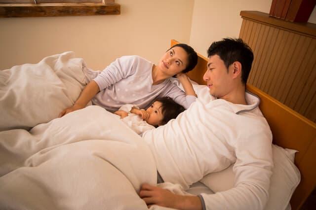 子どもを寝かしつける夫婦