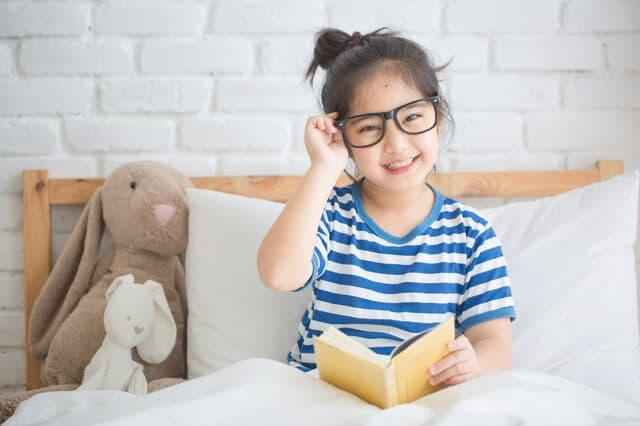 ベッドの上で本を読む女の子