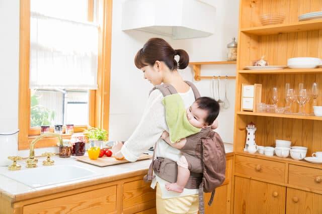 おんぶをしながら料理をする女性