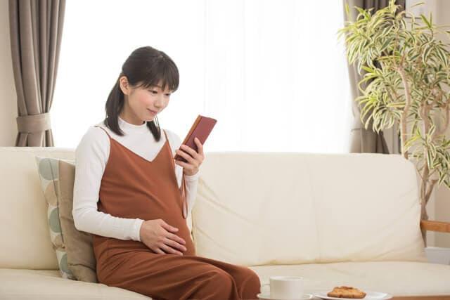 スマートフォンをみる妊婦さん