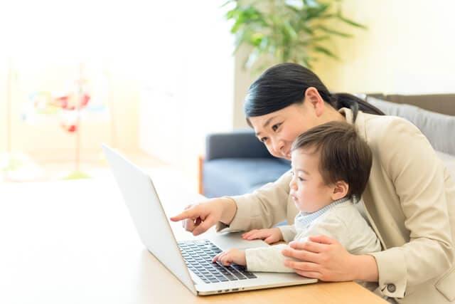 パソコンをみるママと赤ちゃん