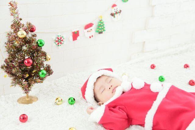 クリスマスツリーの隣で眠る子ども