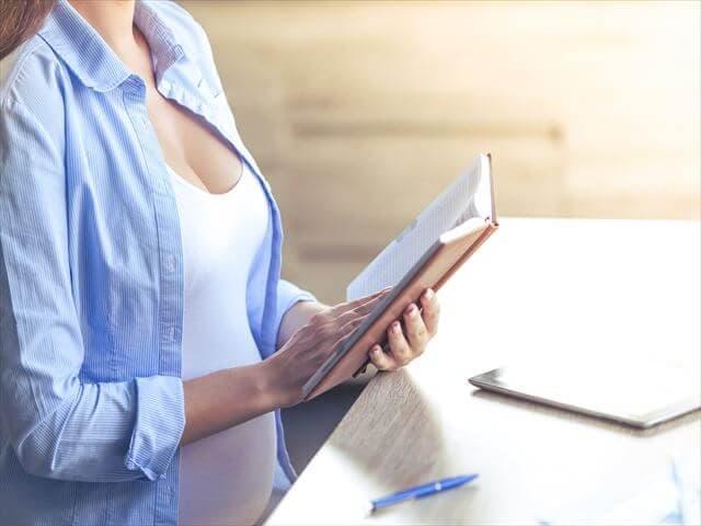 書類を書く妊婦