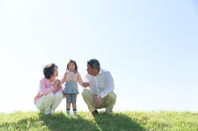 外で遊ぶ祖父母と孫