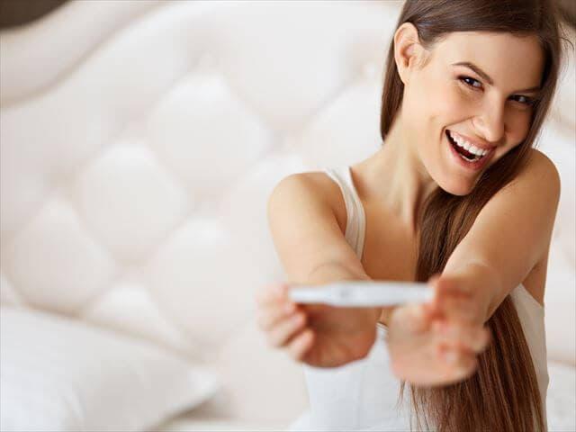 妊娠検査薬を見せる女性