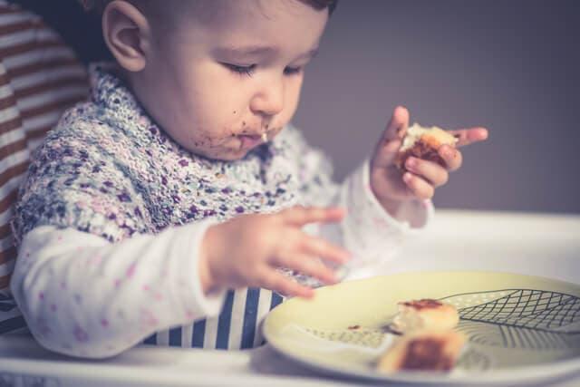 甘いケーキを食べる赤ちゃん