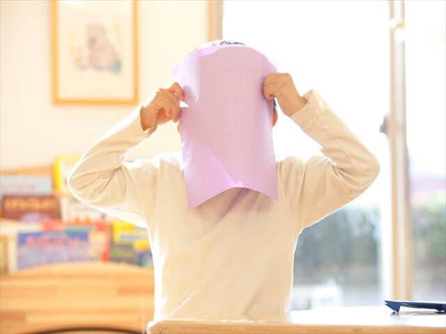 顔を隠す男の子