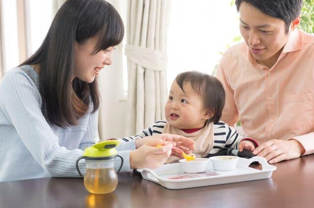 赤ちゃんに離乳食を与える両親