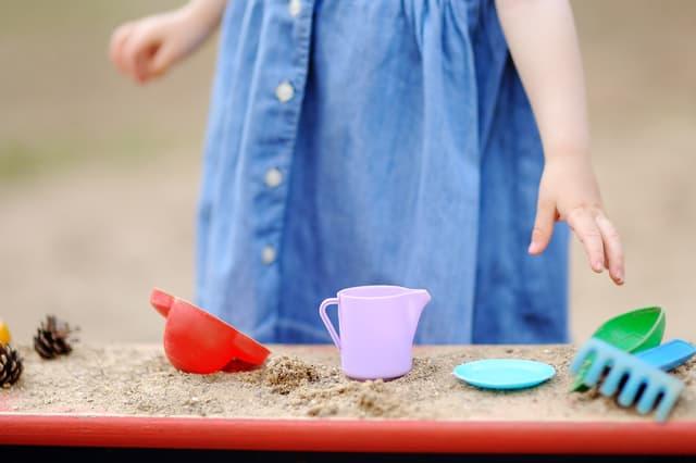 砂場でおもちゃを選ぶ子ども