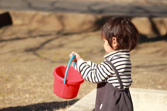 砂場でバケツを持ち上げる子ども