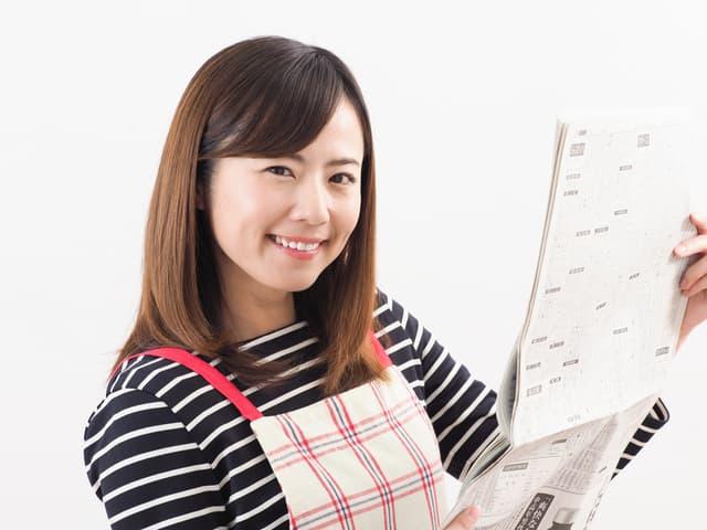 新聞紙を持つ女性